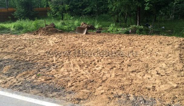 Несколько машин песка под укладку бетонных плит на въезде.